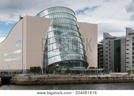 Dublin Ireland - August 7 2017: Closeup of barrel shaped convention center building along Liffey River quay in new financial district. Glass and concrete. Street scene.