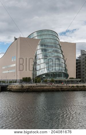 Dublin Ireland - August 7 2017: Portrait closeup of barrel shaped convention center building along Liffey River quay in new financial district. Glass and concrete. Street scene.