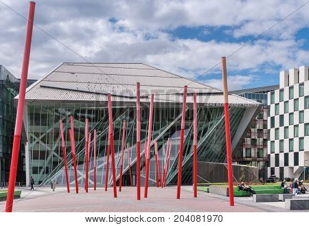 Dublin Ireland - August 7 2017: New modern building of Bord Gais Energy Theater on Grand Canal Square with forest of red sticks art composition in front. Glass Triangles and other shapes. Street scene.