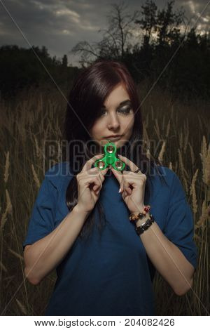 Sad girl with closed eyes posing in a field with fidget spinner