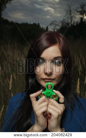 Sad girl with cllosed eyes posing in a field with fidget spinner