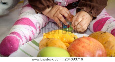 enseñándole unas frutas de diferentes colores y sabores