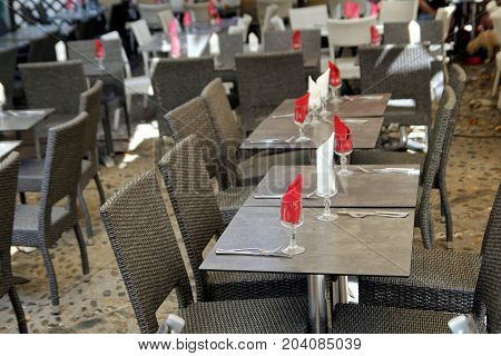 Empty Tables Set With Red And White Napkins At An Outside Restaurant