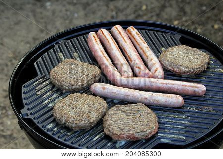 Sausages And Burgers Sizzling On A Barbecue Griddle Plate