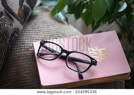 Daily note book with glasses on the couch. The beginning of the school year. Plan daily routine
