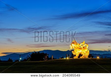 CHIANG RAI THAILAND-OCT. 27 2016: Gold Singha statue at Singha Park is the symbol of Boon Rawd Farm surrounded by the spotlight during the twilight on blue sky background famous tourist destination OCT. 27 2016 in Thailand