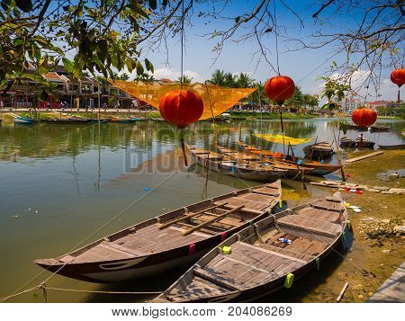HOIAN, VIETNAM, SEPTEMBER, 04 2017: Traditional boats in front of ancient architecture with red lanterns in Hoi An, Vietnam. Hoi An is the World's Cultural heritage site, famous for mixed cultures architecture.