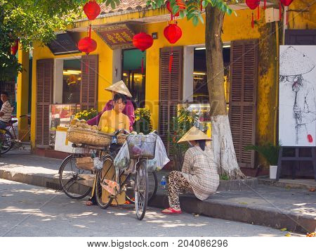 HOIAN, VIETNAM, SEPTEMBER, 04 2017: Unidentified people at street view with old houses, and colorful lanters made of paper, in Hoi An ancient town, UNESCO world heritage.