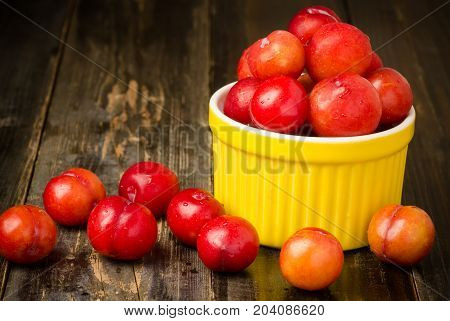 Plum Julee fruit in a yellow bowl on wooden background,healthy fruit