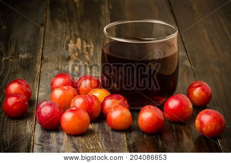 Plum Julee fruit and juice on wooden background,healthy drink
