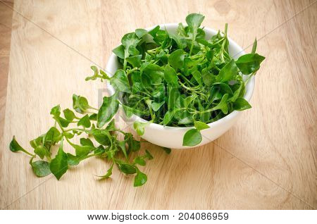 Fresh watercress in a bowl on wooden background,organic vegetables for salad or cooking