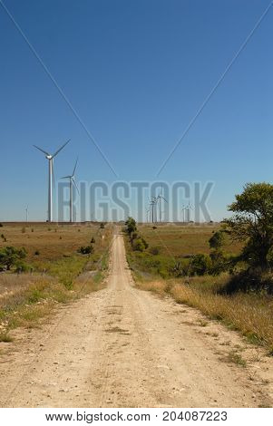 A dirt trail leading into a wind farm located in central Kansas.