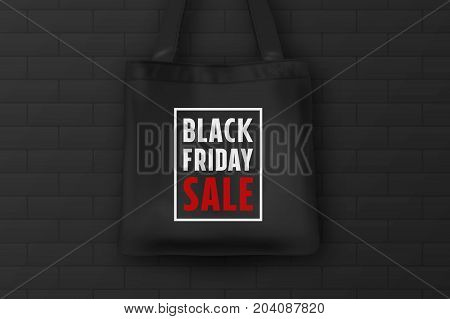 Realistic black textile tote bag with the inscription BLACK FRIDAY SALE. Closeup on brick black wall background. Design template for advertising, branding, mockup. Stock vector. EPS10 illustration.