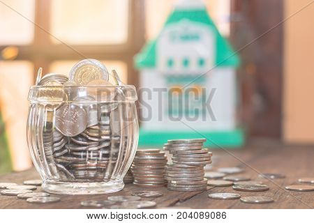 Thailand coins to saving money on bokeh blur background with mini house