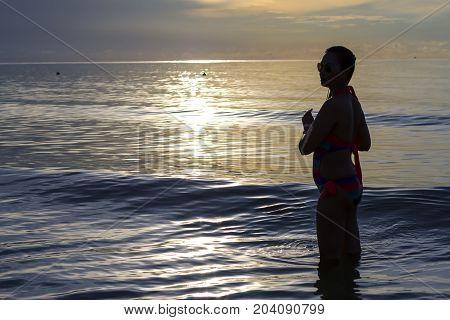 Woman with bikini and sunrise on Thung Wua Lan Beach at Chumphon Province Thailand