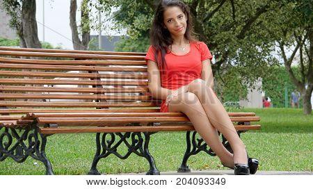 Hispanic Female Sitting on a Park Bench