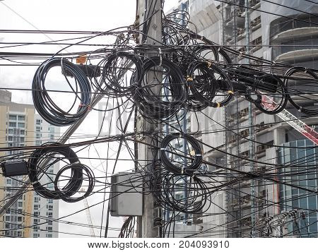 The chaos of cables and wires on every street in Bangkok, Thailand.