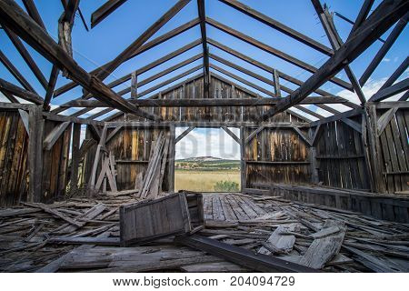 The ruins of a wooden building on the great plains, seen from the inside.