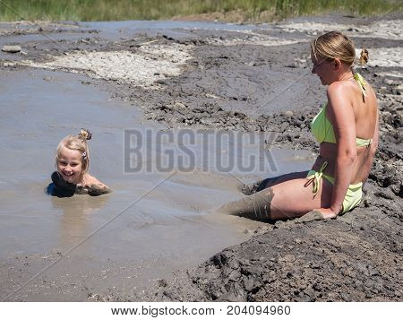 Mother gently bathing my daughter in the mud. Treatment non-traditional methods.