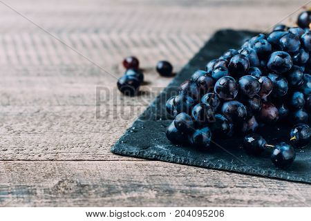 Bunches Of Fresh Ripe Red Grapes On A Wooden Textural Table Background. Dark Grapes, Blue Grapes, Wi