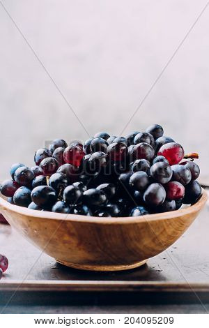 Bunches Of Fresh Ripe Red Grapes In A Wooden Bowl On A Metal Textural Surface Background. Dark Grape
