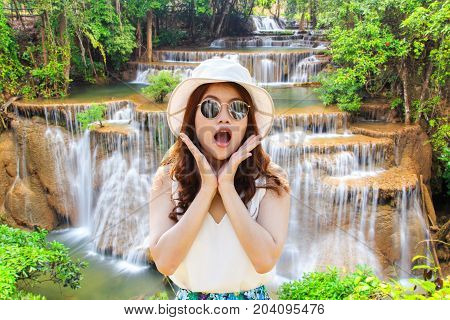 Wow. Close up portrait young asian woman beautiful girl with long red hair looking excited holding her mouth opened amazing waterfall in deep forest at ai Mae Khamin Waterfall.