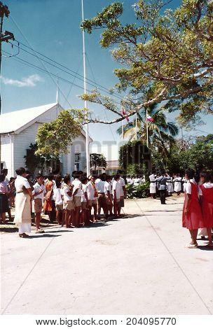 NUKU'ALOFA, TONGATAPU / TONGA - CIRCA 1990: Children in school uniforms gather to watch a parade during a national holiday.