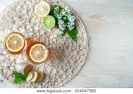 Tea background, top view. Black tea with lemon, ginger, lime, mint, lemon, strawberry. Light green, mint background. Decorated with white cherry flowers.Food industry, tea packing, restaurant business