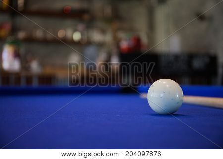 white Billiard ball on blue pool table