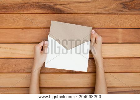 woman hand hold a envelope and post card on the wood desk top view at the studio.
