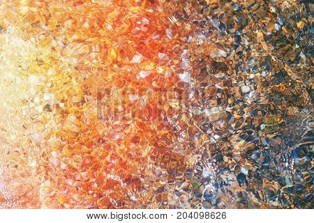 Photo background of transparent sea water with pebbles on the beach