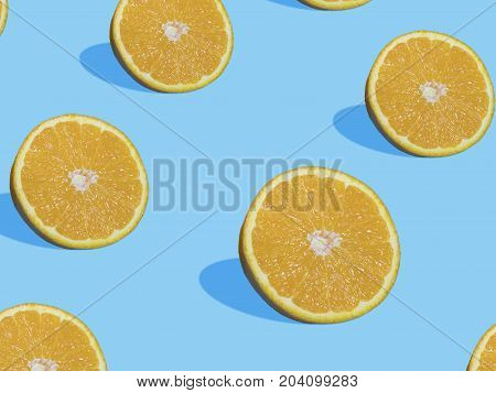 Fresh orange slices on blue background with shadow top view flat lay close up pattern. Summer and healthy citrus fruit concept