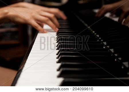 Short focus at the piano key. Woman's hands on the keyboard of the piano closeup