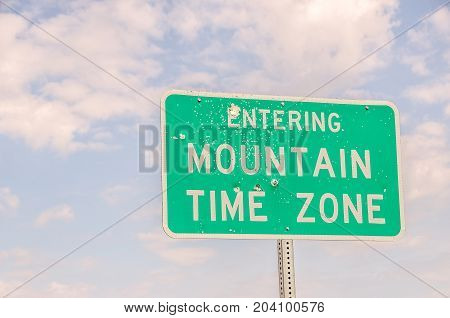 Green and white sign with bullet holes letting travelers know they are entering the central time zone