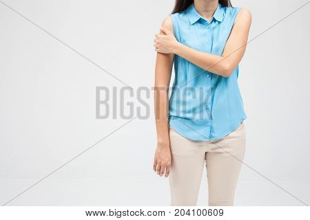 woman with shoulder pain or stiffness on a white wall