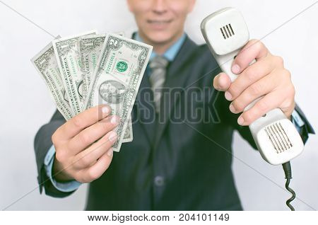Contact us. Call us. Currency exchange. Hot line consultant. Young smiling business man in suit holding phone handset in one hand and money in other hand in front of him.