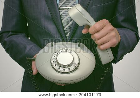 Contact us. Call us. Customer help service. Hot line consultant. Phone talk. Business man in suit holding analog phone handset in front of him.