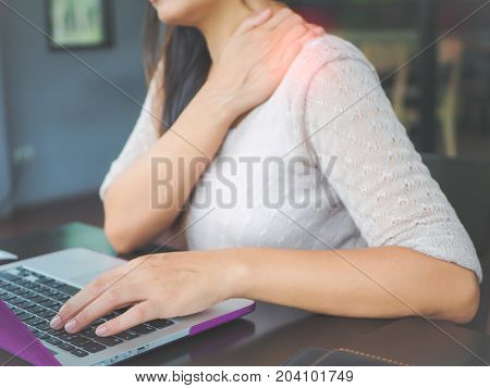 Closeup woman with hands holding her shoulder pain. Office syndrome and Health-care Concept.