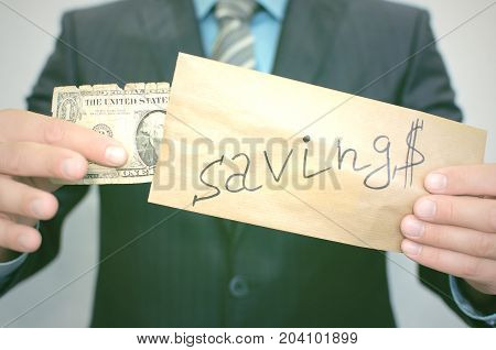 Savings. Poverty. Pay the debts. The man in the suit pulls out an old battered dollar from the envelope with inscription