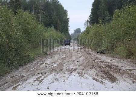 Car Rides On A Rural Forest Road After A Rain With Mud And Deep Puddles