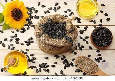 Sunflower Oil, Seeds And Flower On White Wooden Background. Top View