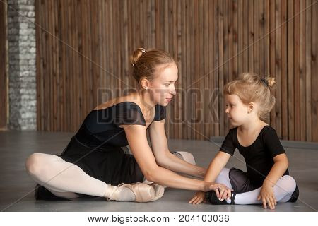 young woman ballerina in a black dress white pantyhose and pointe shoes help stretch before the dance a small inattentive girl in a black dress to dance ballet well in a dark dance studio