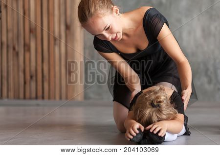 Young blonde female ballerina in a black dress white pantyhose and pointe shoes helps stretch before the dance a small inattentive blonde girl in a black dress to dance ballet well in a dark studio