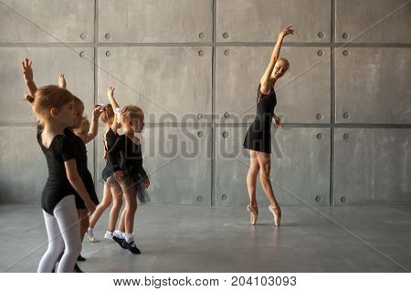 A young ballerina teaches to dance ballet of young girls ballerinas with black dresses white pantyhose and pointe shoes in a dark dance studio