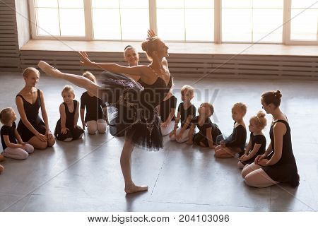 Little girls of the ballerina European and Asian nationalities black dresses and tulle pantyhose are shaken as the ballerina of the prima theater dances in the form of a black swan before the ballet
