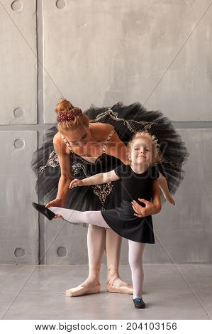 a young woman ballerina in a black dress white pantyhose and pointe shoes teaches to dance the ballet of young girl ballerina in black dresses and tights in a dark dance studio