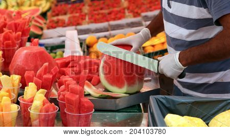 Man Cuts Watermelon With A Large And Sharp Knife To Prepare Frui