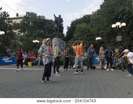 NEW YORK NEW YORK USA - AUGUST 25: People dance in front of George Washington statue inside Union Square park and 14th street. Taken August 25 2017 in New York.