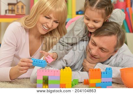 Portrait of parents playing with daughter in room