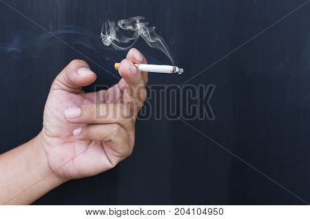 Close up cigarette or tobacco with smoke in hand and copy space